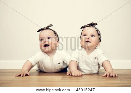 Cute baby twin sisters crawl together on wooden floor wearing funny tiger headbands. Vintage