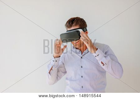 Shot of happy businessman watches content on a virtual reality display. Businessman with virtual reality goggles against grey background.