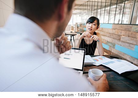 Shot of two businesspeople discussing work while sitting in office. Woman in meeting with office manager.