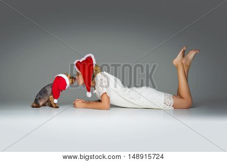 Beautiful girl in lace dress and red santa cap kissing pretty yourkshire terrier in christmas hat. Studio shot over grey background. Copy space.