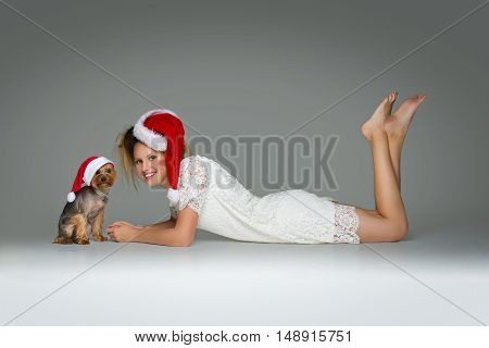 Beautiful girl in lace dress and red santa cap lying with pretty yourkshire terrier in christmas hat. Studio shot over grey background. Copy space.