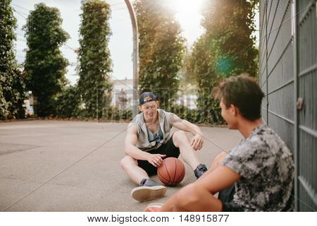 Young Basketball Players Sitting On Court And Smiling