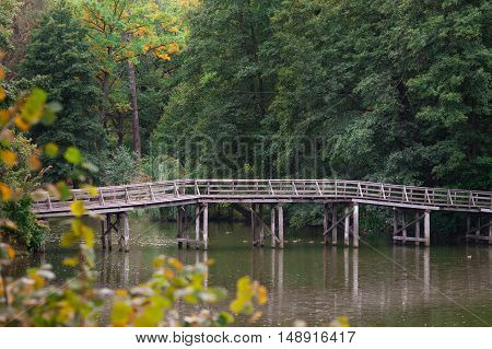 Wooden bridge over the river in summer park.