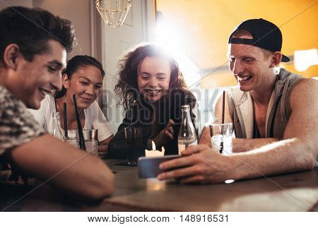 Cheerful young friends looking at smart phone while sitting in cafe. Mixed race people sitting at a table in restaurant using mobile phone.