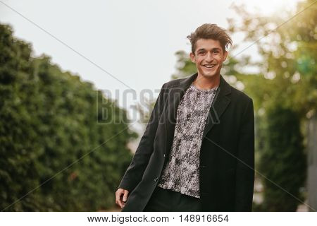 Portrait of handsome young man standing outdoors looking at camera and smiling. Teenage guy in casuals looking happy.