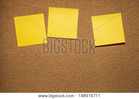 three yellow reminder sticky note on cork board