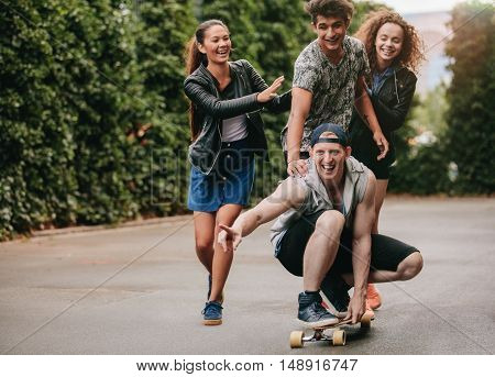 Full length shot of young men on skateboard with women friends pushing them. Group of teenagers enjoying outdoors with skateboard.