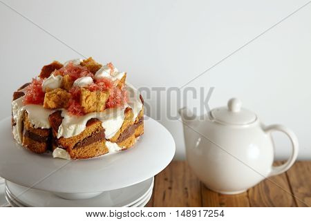 Close up shot of a delicate light brown cake with cream, grapefruit and chocolate filling on a pyramid of white teaware next to a teapot