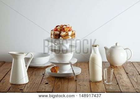 Modern white teaware, a milk bottle and a light brown sponge cake with cream, chocolate filling and grapefruit decorations