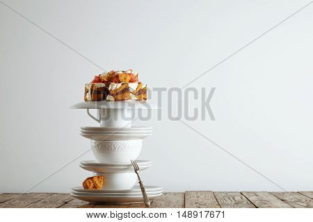 Pyramid of beautiful white porcelain cups and saucers with a nontraditional wedding cake on top
