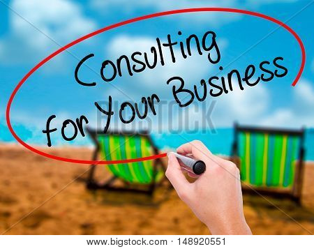 Man Hand Writing Consulting For Your Business With Black Marker On Visual Screen
