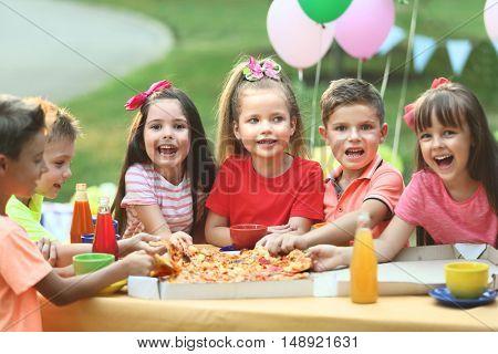 Children eating pizza in park