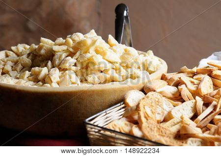 Lot of pieces of parmesan cheese and slices of toasted bread on a table.Elevated view