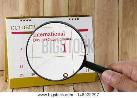 Magnifying glass in hand on calendar you can look International Day of Older Persons on date 01 October concept of a public relations campaign.