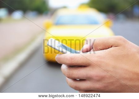 Male hand with cellphone calling taxi
