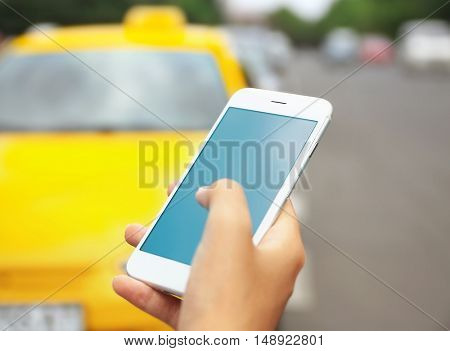 Female hand with cellphone calling taxi