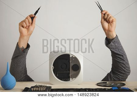 A man's hands with pincers and screwdriver, the man's head is hidden behind a computer, on a white wall background