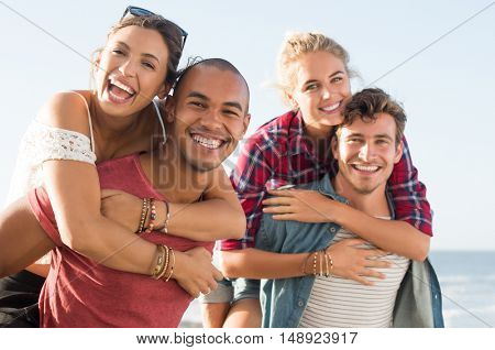 Portrait of happy and cheerful young couples piggyback having fun. Smiling guys piggybacking girls outdoor and looking at camera. Two happy boyfriends and girlfriends together at sunset.