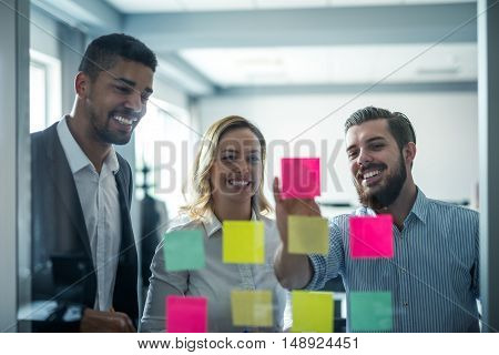 Colleagues looking at sticky notes in an office.