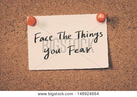 face the things you fear. note on a bulletin board