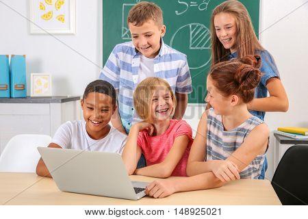 Schoolchildren with laptop in classroom