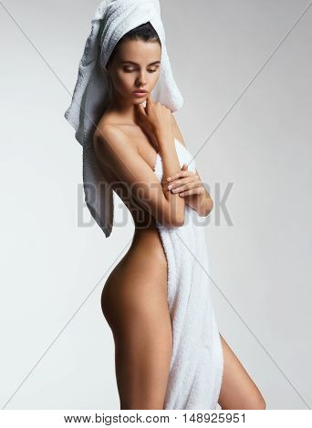Well-groomed young woman after bath. Photo of Sexy body woman on gray background. Wellness and Spa concept.