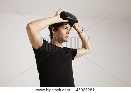Portrait of a young man in black t-shirt putting on VR headset isolated on white