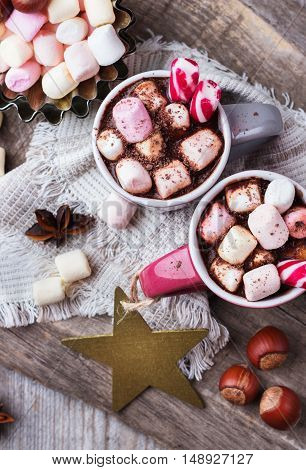 Hot chocolate with marshmallows and spices on rustic wooden table. Selective focus, tasty holidays concept. Drink for fall and winter, christmas beverage. Top view, overhead flat lay