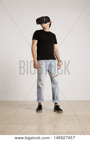 Full body shot of a young male model in VR headset, black unlabeled t-shirt and blue torn jeans looking around the room with white walls and light wooden floor