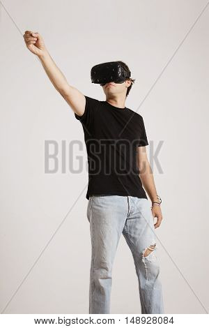 Full body shot of a man in torn jeans and unlabeled black t-shirt wearing VR headset holding something high up isolated on white