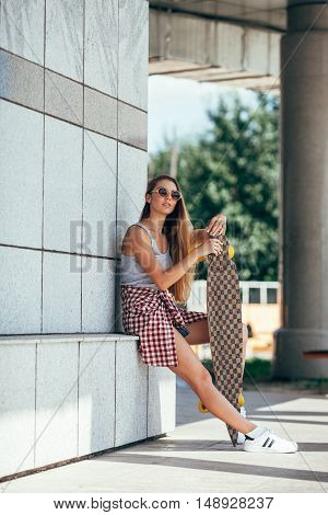 Portrait of beautiful girl wearing sunglasses holding longboard and looking at camera
