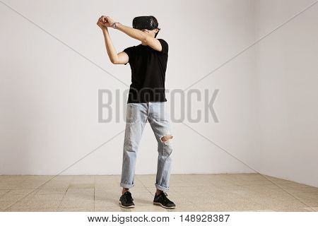 Full length photo of a young caucasian model in light blue torn jeans and black t-shirt playing baseball or tennis in VR glasses