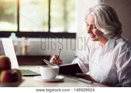 Good morning. Pleasant old women doing her daily business calculations at the kitchen table while having coffee