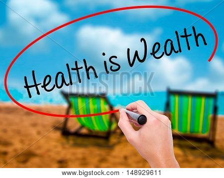 Man Hand Writing Health Is Wealth With Black Marker On Visual Screen