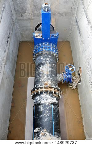 The construction process of node to connect cold water supply. The concrete box with a distribution pipe and valves.