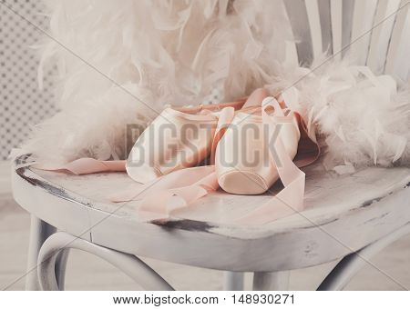 Pastel pink ballet shoes background. New pointe shoes with satin ribbon lay on white rustic shubby chic chair near feather boa