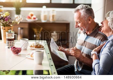 Great start of the day. Nice old couple sitting at kitchen table and laughing while having breakfast with coffee and raspberry