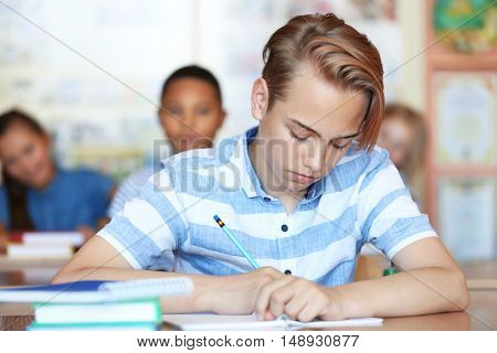 Cute schoolboy on lesson in classroom