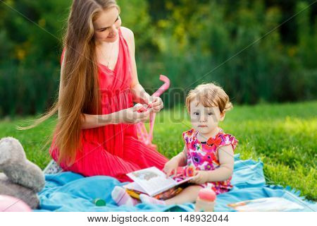 Mum with daughter and toys on picnic in park in summer