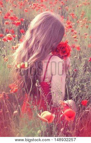 Back View Of A Young Woman With Long Blonde Hair In A Red Dress Sitting In The Poppy Field And Enjoy