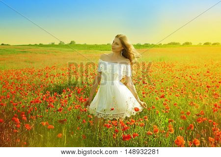Young Happy Woman With Long Blonde Hair In A White Dress Walking In A Poppy Field And Enjoying Beaut
