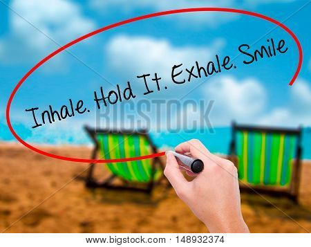 Man Hand Writing Inhale Hold It Exhale Smile With Black Marker On Visual Screen