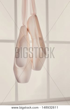 Pastel pink ballet shoes background. New pointe shoes with satin ribbon hanging on window, high-key soft toning, vertical image
