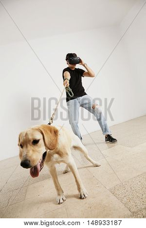 A man in jeans, plain black t-shirt and VR headset holding a light brown lab dog on a leash in a room with white walls and light wooden floors