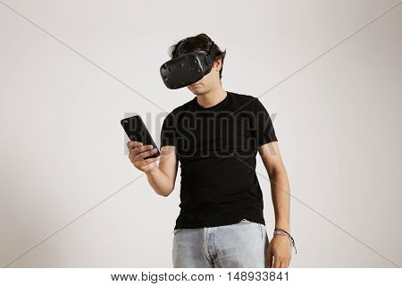 A gamer in VR glasses and plain black t-shirt looking at his smartphone isolated on white