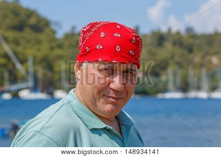 portrait man in red bandana against the backdrop of marina Marmaris