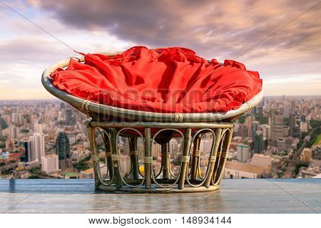 Chairs made of rattan and upholstery fabrics in red on wooden terrace with the backdrop of the city.