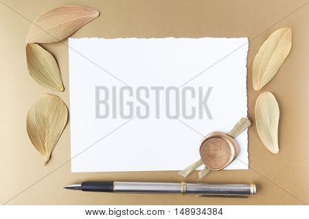 Letter and dry leaves on golden background. Flat lay. Owerhad view