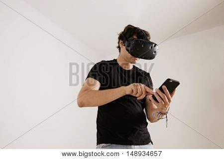 A man in VR glasses and black unlabeled t-shirt swiping on his smartphone's screen against white background