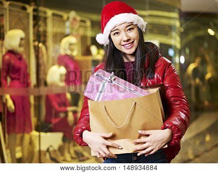 happy young asian woman wearing christmas hat carrying shopping bag